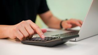 close up bookkeeper employee man hand press on calculator for calculate expenses estimate monthly or company's profit and typing keyboard on laptop for information at office , business concept