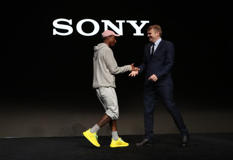 LAS VEGAS, NEVADA - JANUARY 07: Sony Music Entertainment CEO Rob Stringer (R) greets recording artist Pharrell Williams (L) during a Sony press event for CES 2019 at the Las Vegas Convention Center on January 7, 2019 in Las Vegas, Nevada. CES, the world's largest annual consumer technology trade show, runs from January 8-11 and features about 4,500 exhibitors showing off their latest products and services to more than 180,000 attendees. (Photo by Justin Sullivan/Getty Images)