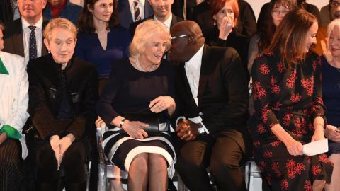 LONDON, ENGLAND - FEBRUARY 19: Camilla, Duchess Of Cornwall sits next to editor-in-chief of British Vogue magazine Edward Enninful during the Bethany Williams Show as she visits London Fashion Week at BFC Show Space on February 19, 2019 in London, England. (Photo by Eddie Mulholland - WPA Pool/Getty Images)