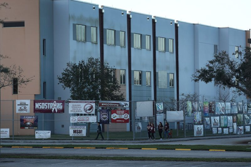 PARKLAND, FLORIDA - FEBRUARY 14:   Students walk past the building where a mass shooting took place at Marjory Stoneman Douglas High School as they arrive for school on February 14, 2019 in Parkland,  Florida. Marjory Stoneman Douglas High school a year ago on Feb. 14th, saw 14 students and three staff members killed during the mass shooting. (Photo by Joe Raedle/Getty Images)