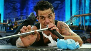 HERTFORDSHIRE, ENGLAND - AUGUST 1:  Singer Robbie Williams performs at Knebworth Park August 1, 2003 in Hertfordshire, England.  (Photo by Jon Furniss/Getty Images)
