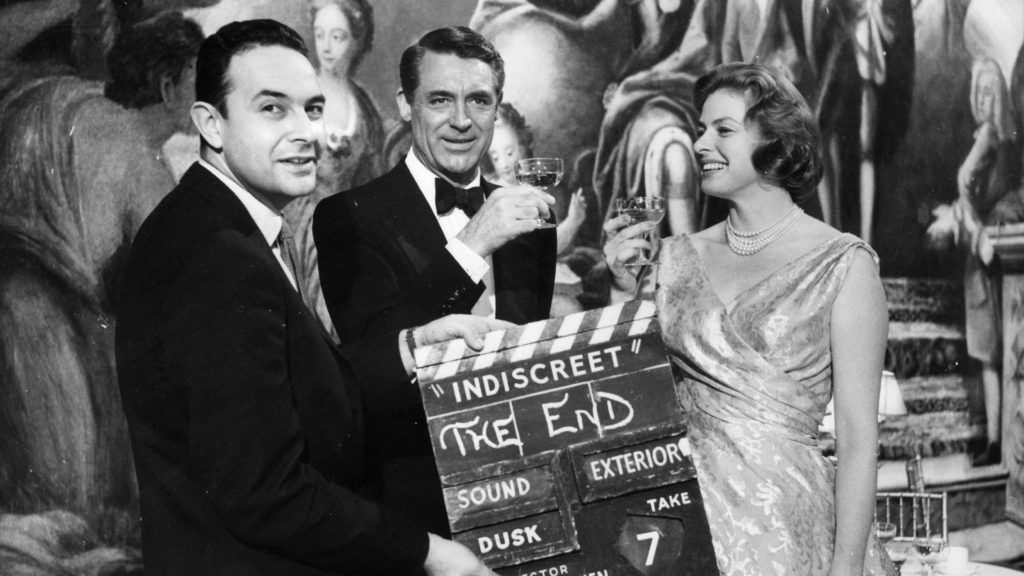 12th February 1958:  Director Stanley Donen holds up the final clapperboard as the stars Cary Grant (1904-1986) and Ingrid Bergman (1915-1982) celebrate the completion of their latest film, 'Indiscreet' at Elstree Studios.  (Photo by Fox Photos/Getty Images)
