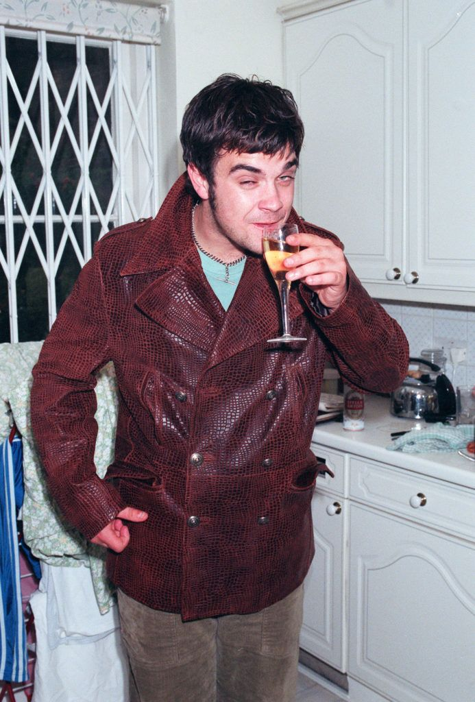 LONDON - 1996: Singer Robbie Williams drinking at his home shortley after leaving Take That. (Photo by Dave Hogan/Getty Images)
