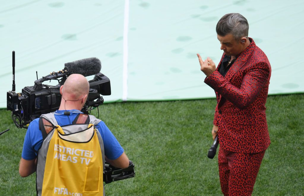 MOSCOW, RUSSIA - JUNE 14:  (EDITORS NOTE: Image contains profanity.) Singer Robbie Williams gestures into a TV camera during the opening ceremony prior to the 2018 FIFA World Cup Russia Group A match between Russia and Saudi Arabia at Luzhniki Stadium on June 14, 2018 in Moscow, Russia.  (Photo by Shaun Botterill/Getty Images)