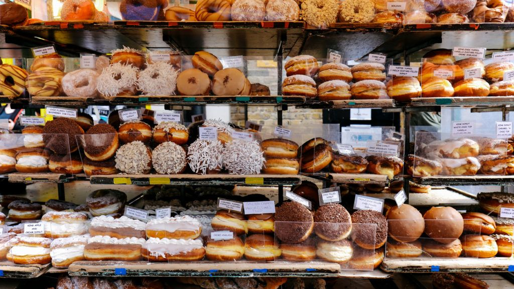 Variety of doughnuts on a market stall in a small street in Camden Town, London, UK