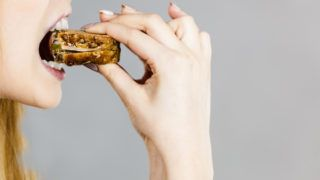 Young woman eating sandwich, taking bite with wide open mouth. Food, calories, dieting concept. Studio shot on grey background, profile view.
