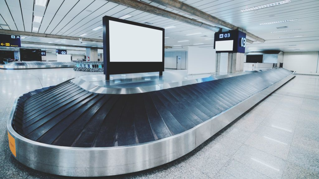 Wide-angle view of a modern baggage conveyor belt in a contemporary airport terminal: multiple ribbon moving sections, chromed body, empty white informational LCD screen template on the top