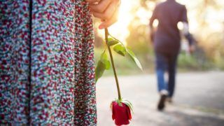 Sadness Love in Ending of Relationship Concept, Broken Heart Woman Standing with a Red Rose on Hand, Blurred Man in Back Side Walking away as background  (Sadness Love in Ending of Relationship Concept, Broken Heart Woman Standing with a Red Rose on H