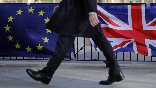 A man walks past the flags of Anti-Brexit protesters outside the Houses of Parliament in London on February 12, 2019. - British Prime Minister Theresa May asked MPs Tuesday to give her more time for talks with the European Union on renegotiating the Brexit deal, just weeks before the scheduled March 29 departure date. (Photo by Tolga AKMEN / AFP)