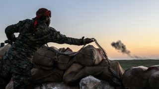 A Syrian Democratic Forces (SDF) fighter arranges an ammunition belt in a hilltop near  the embattled village of Baghouz in Syria's northern Deir Ezzor province on February 19, 2019. - US-backed forces said several jihadists and dozens of civilians quit the Islamic State group's last patch of territory in Syria Tuesday, and warned remaining fighters should surrender or face death. Backed by air strikes by the US-led coalition, the Kurdish-led Syrian Democratic Forces have trapped the jihadists in a segment of Baghhouz village that is less than half a square kilometre (a fifth of a square mile). (Photo by Bulent KILIC / AFP)