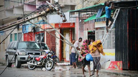 Residents are seen protecting themselves by the rain in the aftermath of the passage of the cyclone Idai in Beira, Mozambique, on March 17, 2019. - More than 120 people have died and many more are missing in Mozambique and neighbouring Zimbabwe on March 17, 2019 after tropical cyclone Idai barrelled across the southern African nations with flash floods and ferocious winds. (Photo by ADRIEN BARBIER / AFP)