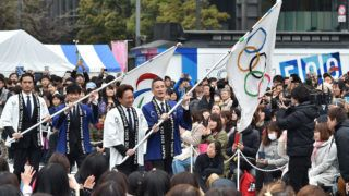 """The flags for the Tokyo 2020 Olympic and Paralympic games arrive at Tokyo Station during the final event of the Tokyo 2020 Olympic Flag and Paralympic Flag Tour, """"Tokyo 2020 500 Days to Go"""", on March 30, 2019. - Tokyo 2020 Olympic Flag and Paralympic Flag Tours have visited all of the 62 wards, villages, town and cities that make up the Tokyo metropolitan area, and all 47 of Japan's prefectures, since the launch on October 2016. (Photo by Kazuhiro NOGI / AFP)"""