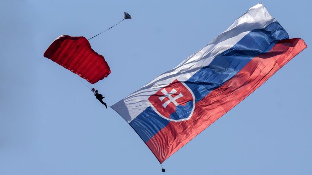 A soldier jumps with parachute and giant Slovak flag (9 meters wide and 16 meters long to commemorate the 71st anniversary of the Slovakia's National Uprising (SNP)  during the Slovak International Air Fest SIAF 2015 at the Slovak Airforce Base of Sliac on August 29, 2015. AFP PHOTO / JOE KLAMAR (Photo by JOE KLAMAR / AFP)