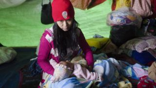 Internally displaced mother Seng Moon, fleeing renewed fighting between Myanmar's army and ethnic insurgents in the country's remote north, waits in a temporary shelter with her one-month-old daughter in Danai, Kachin state, on May 12, 2018. - At least 19 people have been killed in clashes between Myanmar's military and an ethnic armed group on May 12 in northern Shan State, Myanmar army and local sources told AFP, the most deadly flare-up in recent years as fighting in the borderlands intensifies. (Photo by Ye Aung Thu / AFP)