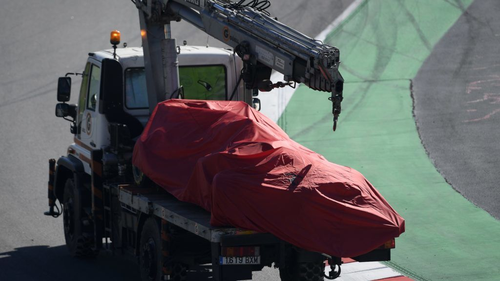 A truck carries the Ferrari of German driver Sebastian Vettel after he crashed into the barriers during the tests for the new Formula One Grand Prix season at the Circuit de Catalunya in Montmelo in the outskirts of Barcelona on February 27, 2019. (Photo by LLUIS GENE / AFP)