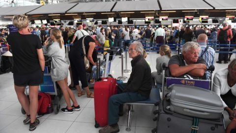 Stranded passengers wait at the check-in area at the Suvarnabhumi International Airport in Bangkok on February 28, 2019. - Thai airways cancelled 11 European-bound flights after Pakistan closed its airspace as tensions with India mount, the carrier said February 28, a move affecting thousands of passengers at the height of the country's busy tourist season. (Photo by Lillian SUWANRUMPHA / AFP)