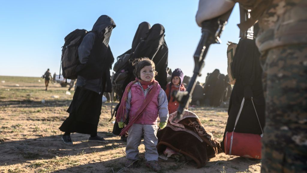 Women and children await to be searched by members of the Kurdish-led Syrian Democratic Forces (SDF) after leaving the Islamic State (IS) group's last holdout of Baghouz, in the eastern Syrian Deir Ezzor province on March 1, 2019. (Photo by Bulent KILIC / AFP)
