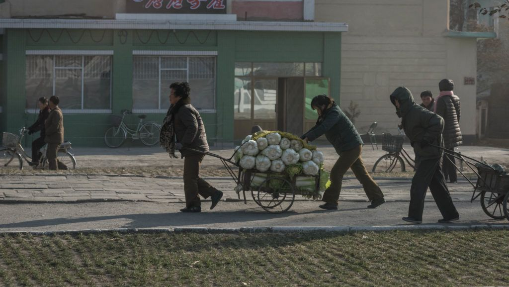 (FILES) A file photo taken on November 22, 2017 shows people pushing a cart carrying cabbage in Hamhung on North Korea's northeast coast. - North Korea recorded its worst harvest for more than a decade last year, the United Nations said on March 6, 2019, as natural disasters combined with its lack of arable land and inefficient agriculture to hit production. (Photo by Ed JONES / AFP)