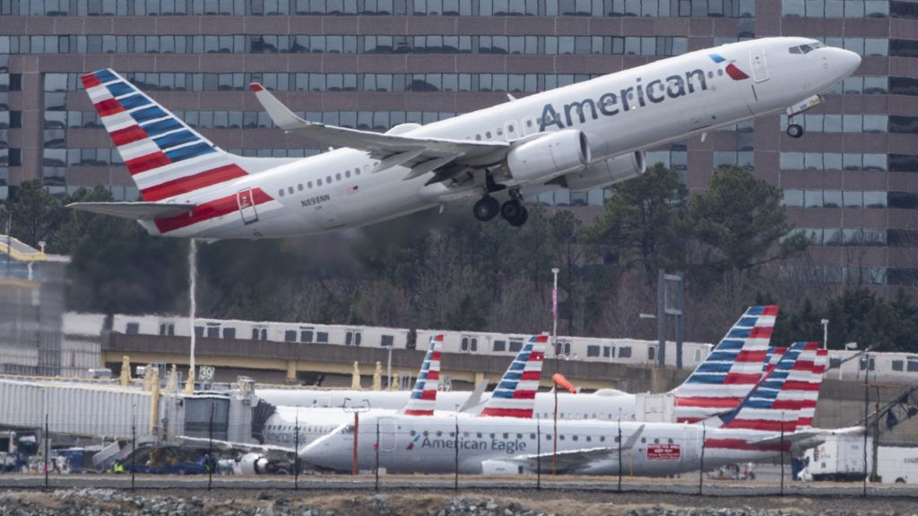 """(FILES) In this file photo taken on March 11, 2019 A Boeing 737 flown by American Airlines passes by the Lockheed Martin building as it takes off from Ronald Reagan Washington National Airport in Arlington, Virginia. - US President Donald Trump on March 13, 2019, announced a plan to ground all Boeing 737 MAX aircraft amid intense international and political pressure following the second deadly crash in less than five months. """"We're going to be issuing an emergency order of prohibition regarding all flights of the 737 MAX 8 and 737 MAX 9,"""" Trump told reporters the White House. (Photo by Andrew CABALLERO-REYNOLDS / AFP)"""