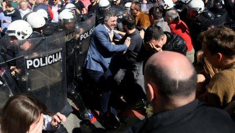 Right-wing Dveri party leader Bosko Obradovic (C) scuffles with police forces during a demonstration against Serbian President Aleksandar Vucic outside the presidential building in Belgrade, on March 17, 2019. - Opposition supporters gathered outside the presidential building during a press conference of Serbian President Aleksandar Vucic, a day after opponents broke into the state-run RTS television building, demanding to address the population, in images aired live. There have been weekly opposition protests since December against what they describe as Vucic's slide towards autocratic rule, while accusing RTS of pandering to the ruling party and demanding more airtime for opposing views. (Photo by Oliver BUNIC / AFP)