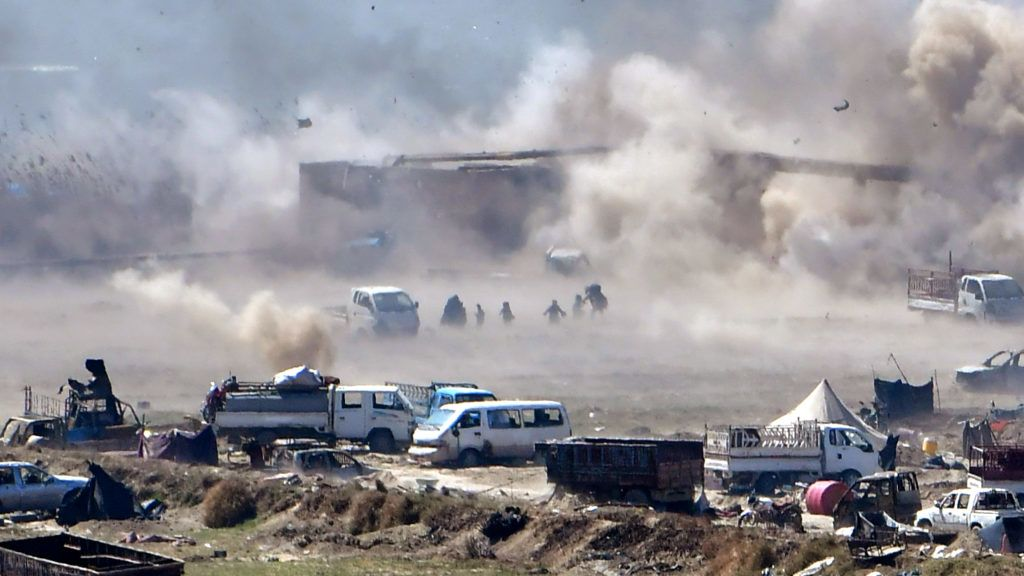 People are seen fleeing as heavy smoke rises above the Islamic State (IS) group's last remaining position in the village of Baghouz during battles with the Syrian Democratic Forces (SDF), in the countryside of the eastern Syrian province of Deir Ezzor on March 18, 2019. - A shroud of black smoke covered the Islamic State group's last Syria redoubt today as US-backed forces battled holdout jihadists after a night of shelling and heavy air strikes. The Kurdish-led SDF have been closing in on IS fighters holed up in a small sliver of territory in the village of Baghouz in eastern Syria since January. (Photo by GIUSEPPE CACACE / AFP)