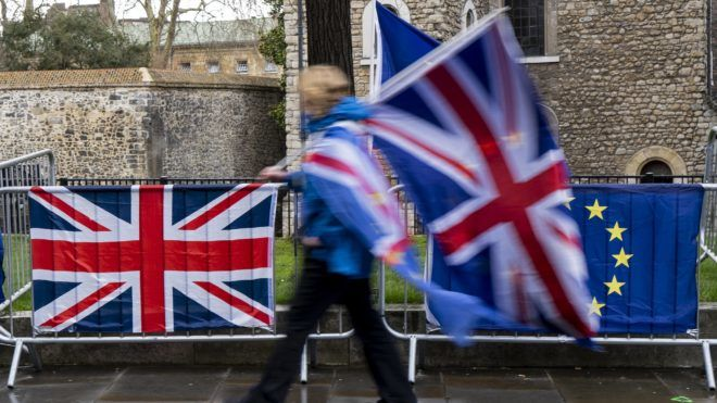 """A protester carrying flags walks past the Union (L) and EU flags of anti-Brexit activists near the Houses of Parliament in London on March 18, 2019. - Britain's government cannot submit its Brexit deal for another vote in parliament if it is """"the same"""" or """"substantially the same"""" to the one already rejected by MPs, the House of Commons speaker said on Monday. """"What the government cannot legitimately do is to re-submit to the House the same proposition or substantially the same proposition,"""" John Bercow told parliament. (Photo by Niklas HALLE'N / AFP)"""
