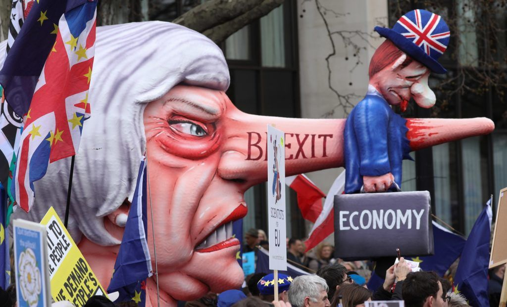 A puppet head of Britain's Prime Minister Theresa May spearing a representation of the British Economy is taken on a march and rally organised by the pro-European People's Vote campaign for a second EU referendum in central London on March 23, 2019. - Hundreds of thousands of pro-Europeans from across Britain were expected to march through London on Saturday calling for another referendum on EU membership with the country mired in political paralysis over Brexit. (Photo by Isabel INFANTES / AFP)