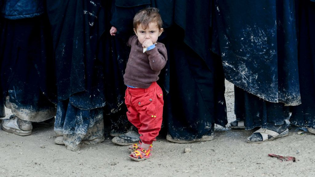 A child stands in queue in al-Hol camp which houses relatives of Islamic State (IS) group members, in al-Hasakeh governorate in northeastern Syria on March 28, 2019. (Photo by GIUSEPPE CACACE / AFP)