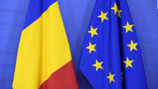 A picture taken on February 16, 2017 at the European Union's Commission headquarters in Brussels shows a flag of the European Union Commission and a Romanian national flag. (Photo by THIERRY CHARLIER / AFP)