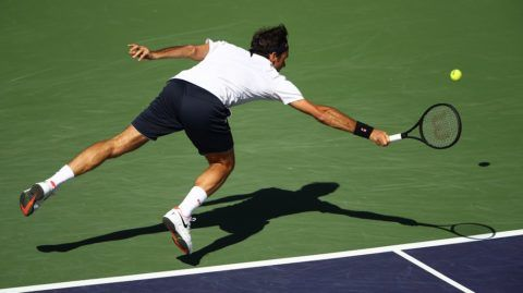 INDIAN WELLS, CALIFORNIA - MARCH 13: Roger Federer of Switzerland dives to play a backhand against Kyle Edmund of Great Britain during their men's singles fourth round match on day ten of the BNP Paribas Open at the Indian Wells Tennis Garden on March 13, 2019 in Indian Wells, California.   Clive Brunskill/Getty Images/AFP