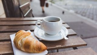 Breakfast with black coffee and croissants on the wooden table in an outdoor cafe. City on a background. Relax time