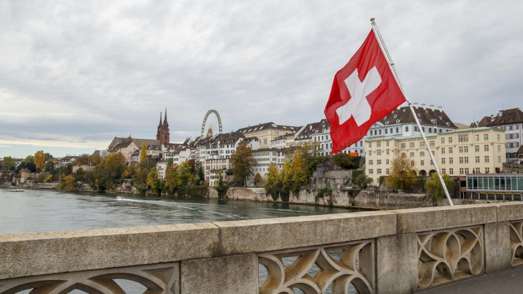 Swiss flag over the river Rhine in Basel, with the Munster and ferris wheel in the background