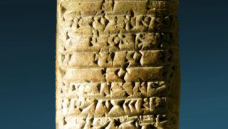 Ancient cuneiform writing on stone on blue background.
