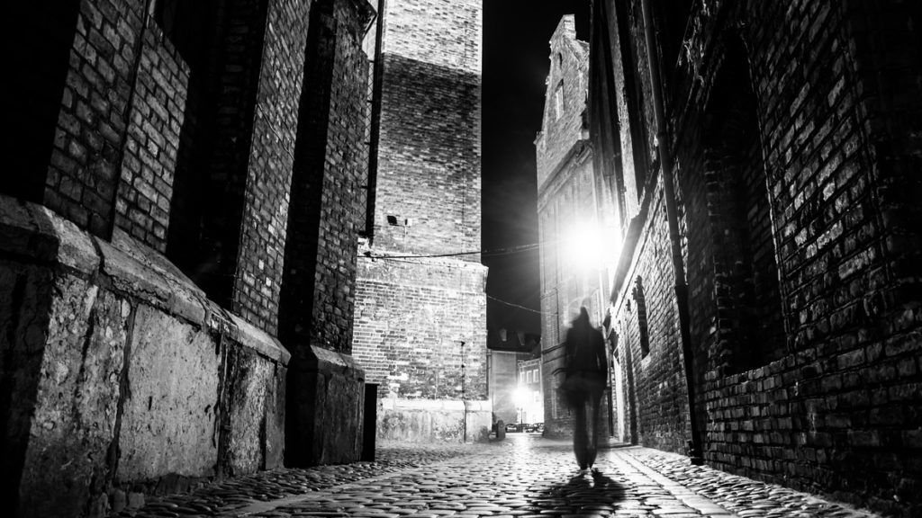 Illuminated cobbled street with light reflections on cobblestones in old historical city by night. Dark blurred silhouette of person evokes Jack the Ripper. Black and white image.
