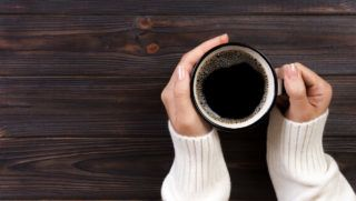 Lonely woman drinking coffee in the morning, top view of female hands holding cup of hot beverage on wooden desk.