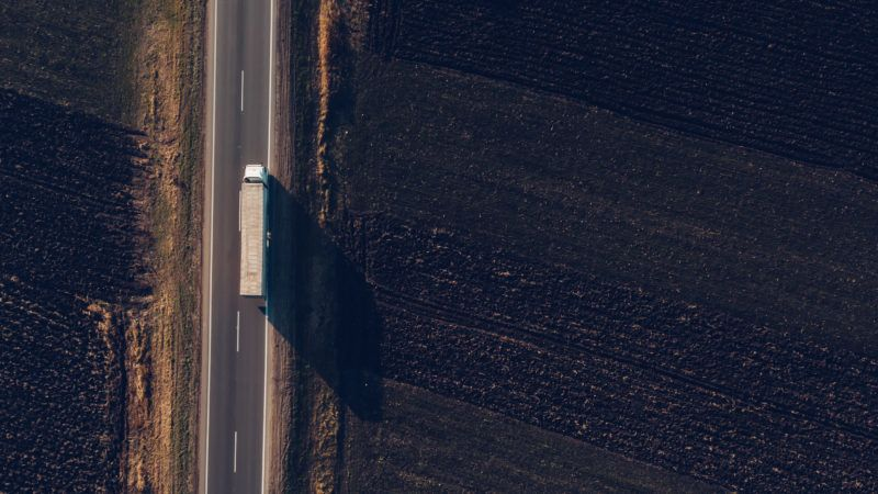 Aerial view of freight transportation truck on the road through countryside