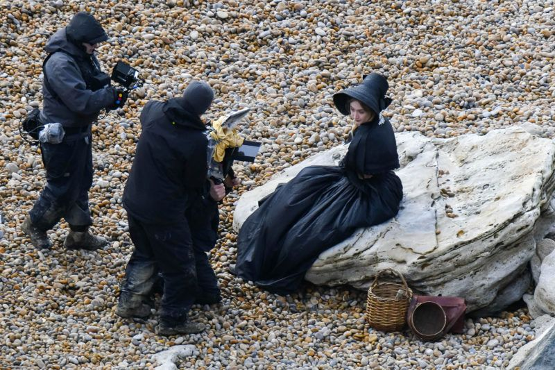 BNPS.co.uk (01202 558833) Pic: Graham Hunt/BNPS  Saoirse Ronan filming a scene on the Beach at Eype near Bridport in Dorset yesterday for the new film Ammonite about the life of fossil hunter Mary Anning.  Saoire Ronan being filmed sitting on a rock. March 14, 2019  ***EXCLUSIVE***