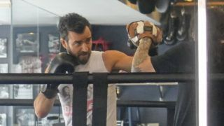 03/14/2019 Justin Theroux puts on the gloves for a sparring session at the local gym in New York City. The 47 year old actor wore a graphic white tank top, Adidas track pants, and black trainers.