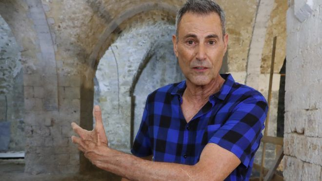 Israeli illusionist and television personality Uri Geller addresses the media during work on his museum in Jaffa on the outskirts of the Israeli coastal city of Tel Aviv on August 14, 2018. - An impressive masbena - or soap-manufacturing factory - that dates back to the 19th-century along with several large underground chambers have been unexpectedly unearthed at the Uri Geller Museum now under construction in the Old City of Jaffa. (Photo by JACK GUEZ / AFP)