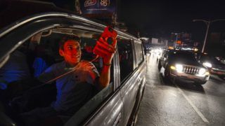 People use their mobile phones at the Francisco Fajardo highway -where they can get telephone service- during a partial power outage in Caracas on March 9, 2019. - Venezuela President Nicolas Maduro claimed that a new cyber attack had prevented authorities from restoring power throughout the country following a blackout on March 7 that caused chaos. The government blamed the outage on US sabotage at the central generator in Guri, in the country's south, which provides 80 percent of Venezuela with its electricity. (Photo by Matias DELACROIX / AFP)