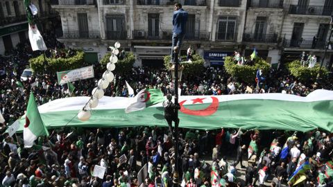 """Algerians carry a giant national flag as they take part in an anti-government demonstration, on April 5, 2019 in the capital Algiers. - Algerians were gathered today for the first mass protests since the resignation of ailing president Abdelaziz Bouteflika, in a key test of whether the momentum for reform can be maintained. Opponents of the old regime have called for a massive turnout, targeting a triumvirate they dub the """"3B"""" -- Abdelakder Bensalah, Tayeb Belaiz and Prime Minister Noureddine Bedoui. (Photo by RYAD KRAMDI / AFP)"""