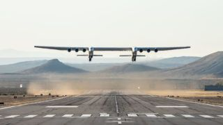 """This handout photograph obtained courtesy of Stratolaunch shows the Stratolaunch plane flying above the California desert, April 13, 2019, the first test flight of the US company's gigantic aircraft whose wingspan is almost half that of an Airbus A380. - The world's largest airplane -- a Stratolaunch behemoth with two fuselages and six Boeing 747 engines -- made its first test flight on Saturday, April 13, 2019 in California. The strange aircraft, built by the legendary aeronautical engineering company Scaled Composites in the Mojave Desert, has two fuselages and is powered by six Boeing 747 engines.  It must theoretically be used to carry and drop at altitude a small rocket that will then light its engine, and will propel to space to place satellites in orbit. This is a more flexible method of accessing the space than vertical rocket takeoffs, as a large take-off runway would suffice. (Photo by Handout / Stratolaunch Systems Corp / AFP) / == RESTRICTED TO EDITORIAL USE  / MANDATORY CREDIT:  """"AFP PHOTO /  STRATOLAUNCH"""" /  NO MARKETING / NO ADVERTISING CAMPAIGNS /  DISTRIBUTED AS A SERVICE TO CLIENTS  =="""