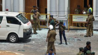 Sri Lankan security personnel stand next to an ambulance outside St. Anthony's Shrine in Kochchikade in Colombo on April 21, 2019 following a blast at the church. - At least 42 people were killed April 21 in a string of blasts at hotels and churches in Sri Lanka as worshippers attended Easter services, a police official told AFP. (Photo by ISHARA S.  KODIKARA / AFP)