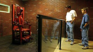 """Jim Wilde (L) and his son Wilson (R) view the electric chair nicknamed """"Old Sparky"""" on display at the Texas Prison Museum in Huntsville, Texas 07 December 2002. The chair, in service from 1924 through 1964, was used to execute 361 prisoners.   AFP PHOTO/Paul BUCK (Photo by PAUL BUCK / AFP)"""