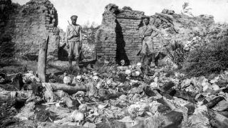 A picture released by the Armenian Genocide Museum-Institute dated 1915 purportedly shows soldiers standing over skulls of victims from the Armenian village of Sheyxalan in the Mush valley, on the Caucasus front during the First World War. Armenians say up to 1.5 million of their forebears were killed in a 1915-16 genocide by Turkey's former Ottoman Empire. Turkey says 500,000 died and ascribes the toll to fighting and starvation during World War I. AFP PHOTO / ARMENIAN GENOCIDE MUSEUM INSTITUTE (Photo by STR / AGMI / AFP)