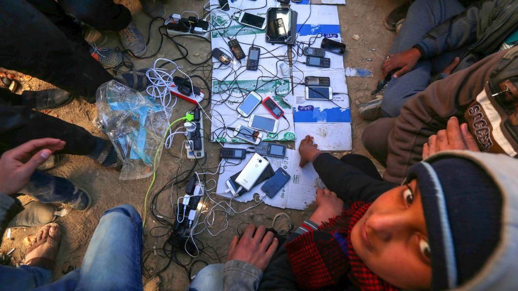 Displaced Iraqis, who fled the violence in the northern city of Mosul as a result of a planned operation to retake the Iraqi city from jihadists, charge their mobile phones at the al-Khazar camp on November 25, 2016, in the village of Hasan Sham, some 40 kilometres east of Arbil. - Iraqi forces should create safe exits for Mosul residents because they cannot protect civilians and wage fierce battles with jihadists at the same time, the International Rescue Committee said.The an aid group also predicted that the fighting to retake the Islamic State group's northern stronghold would last until the spring of 2017 and worried that the trapped population would run out of supplies or take huge risks to flee. (Photo by SAFIN HAMED / AFP)