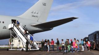 Venezuelan refugees board a Brazilian Air Force plane, heading to Manaus and Sao Paulo, at Boa Vista airport, Roraima state, north of Brazil on May 4, 2018. - The Brazilian government initiated a program of internalisation of refugees who arrive in Boa Vista through the border with Venezuela. In the first phase of the programme they will be relocated in the cities of Sao Paulo, Manaus and Cuiaba. (Photo by EVARISTO SA / AFP)