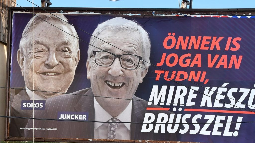 """A picture taken on February 26, 2019 in Budapest shows a billboard bearing portraits of European Commission chief Jean-Claude Juncker (R) and Hungarian-born US investor and philanthropist George Soros and a slogan reading """"You too have a right to know what Brussels is preparing"""". - Opposition activists in Hungary on February 25, 2019 defaced hundreds of posters put up by the government of nationalist Prime Minister Viktor Orban attacking European Commission chief Jean-Claude Juncker and billionaire George Soros. (Photo by ATTILA KISBENEDEK / AFP)"""