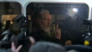 A video grab taken from AFP TV footage shows WikiLeaks founder Julian Assange as he is driven by British Police to Westminster Magistrates Court in London on April 11, 2019. - WikiLeaks founder Assange appeared in a London courtroom on Thursday, hours after being arrested in Ecuador's embassy on an extradition request from the United States and for breaching bail in Britain. (Photo by - / AFP)