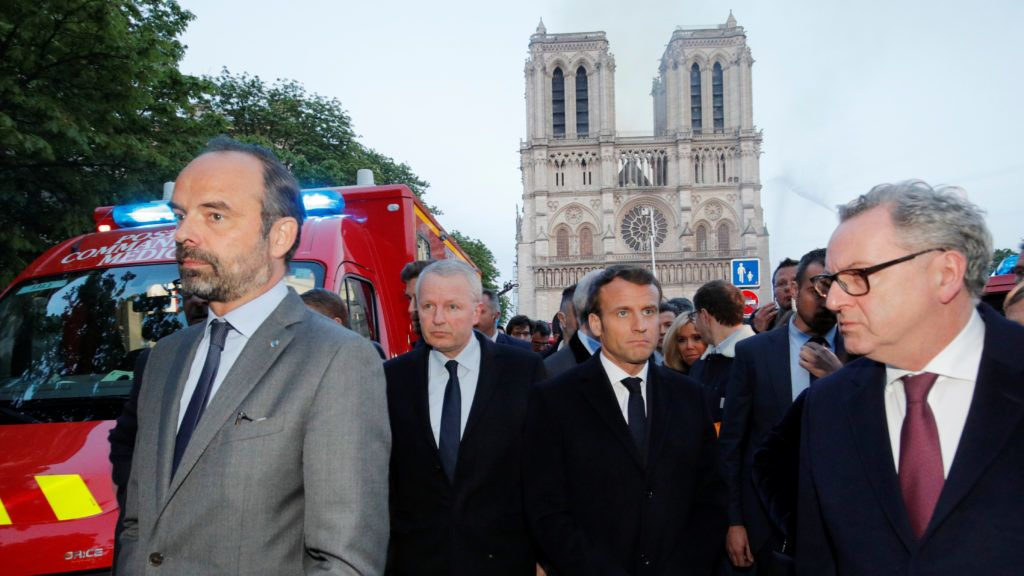 French Prime Minister Edouard Philippe (L), and French President Emmanuel Macron (3rd L) gather in near the entrance of the Notre-Dame de Paris Cathedral in Paris, as flames engulf its roof on April 15, 2019. - A huge fire swept through the roof of the famed Notre-Dame Cathedral in central Paris on April 15, 2019, sending flames and huge clouds of grey smoke billowing into the sky. The flames and smoke plumed from the spire and roof of the gothic cathedral, visited by millions of people a year. A spokesman for the cathedral told AFP that the wooden structure supporting the roof was being gutted by the blaze. (Photo by PHILIPPE WOJAZER / POOL / AFP)